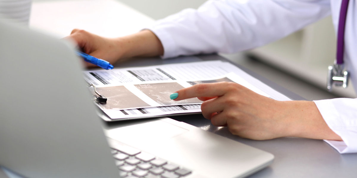 closeup of woman doctor working on computer reviewing charts on a clipboard